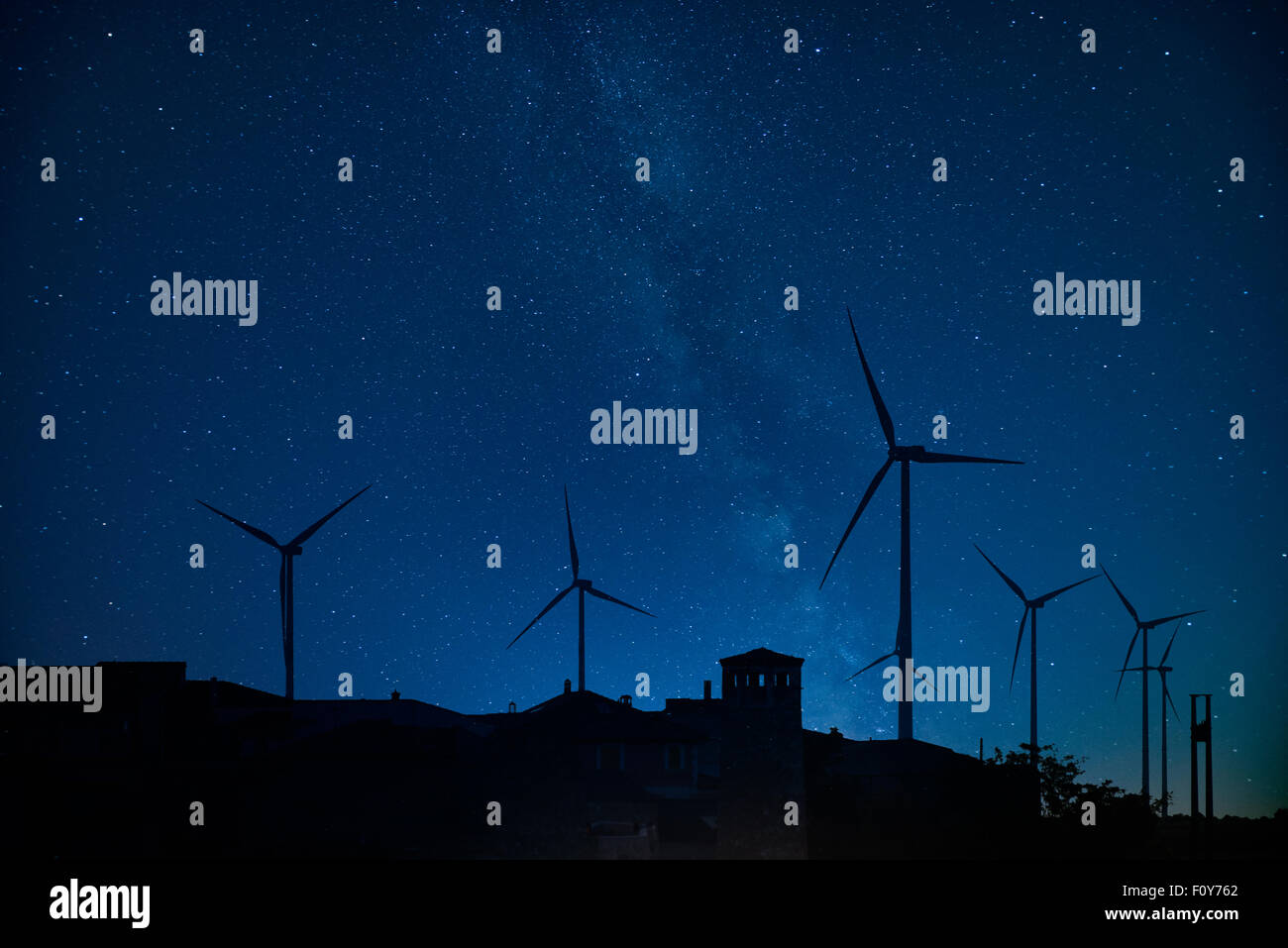Milky way behind a windmill farm. - Stock Image