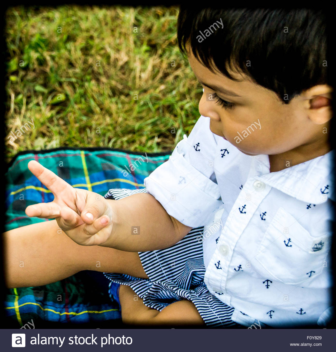 Latino child sitting outside and counting on his fingers - Stock Image