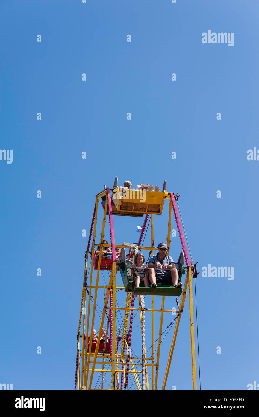 people adults and children sitting in the chairs of fairground ride the big wheel pictured against a clear blue - Stock Image