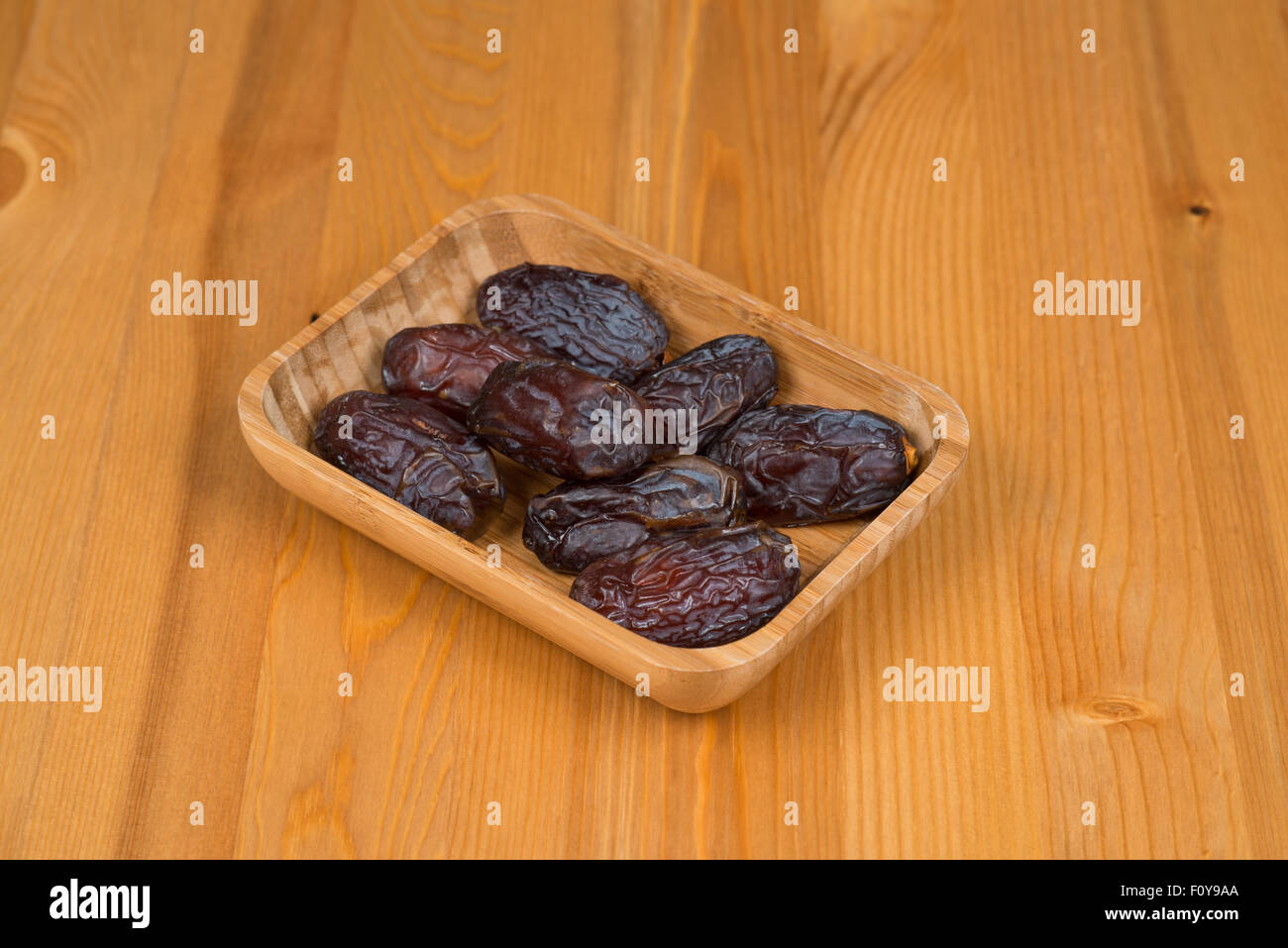 Bowl of dried dates on a wooden background - Stock Image
