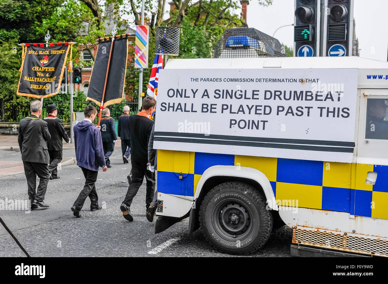 Belfast, Northern Ireland. 23 Aug 2015 - Standard bearers pass a PSNI landrover with a notice saying 'The Parades - Stock Image