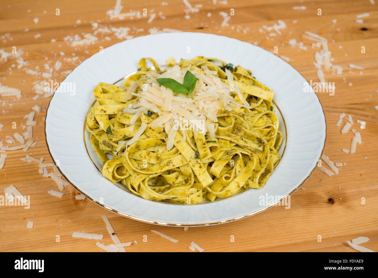 Tagliatelle pasta with pesto sauce and basil leafs on white plate, wood background - Stock Image