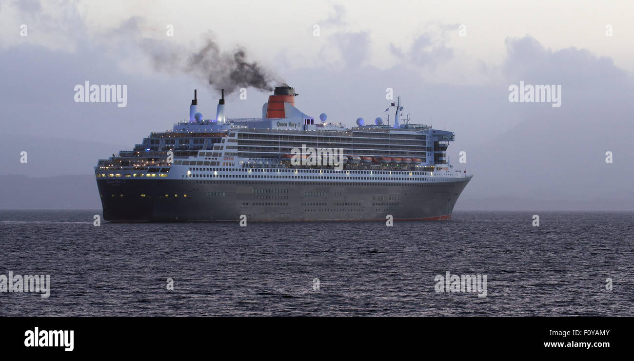 RMS Queen Mary 2 sailing off at Sunset from Maiden Island, Oban, Scotland - Stock Image