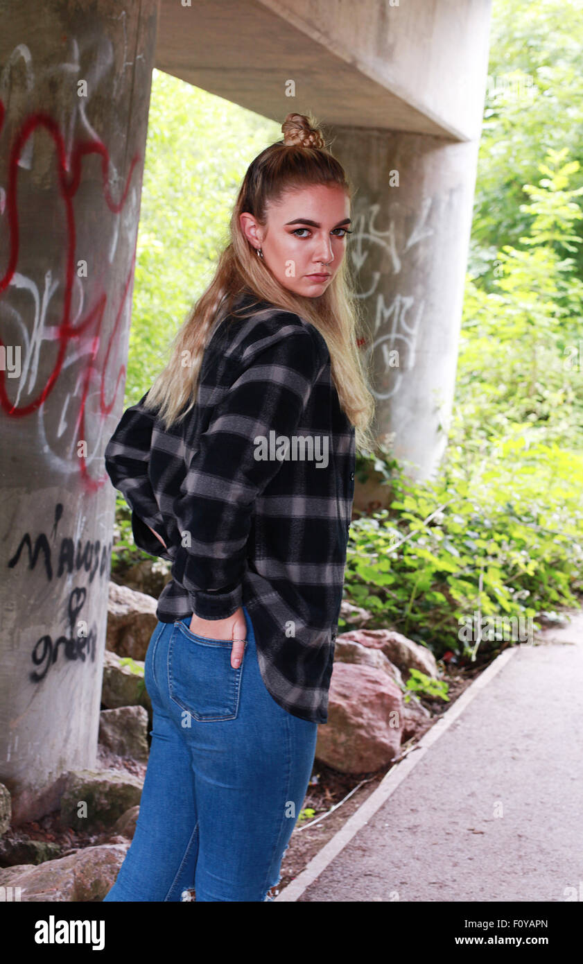 Tough moody teenage girl in an urban location wearing a septum in her nose. - Stock Image