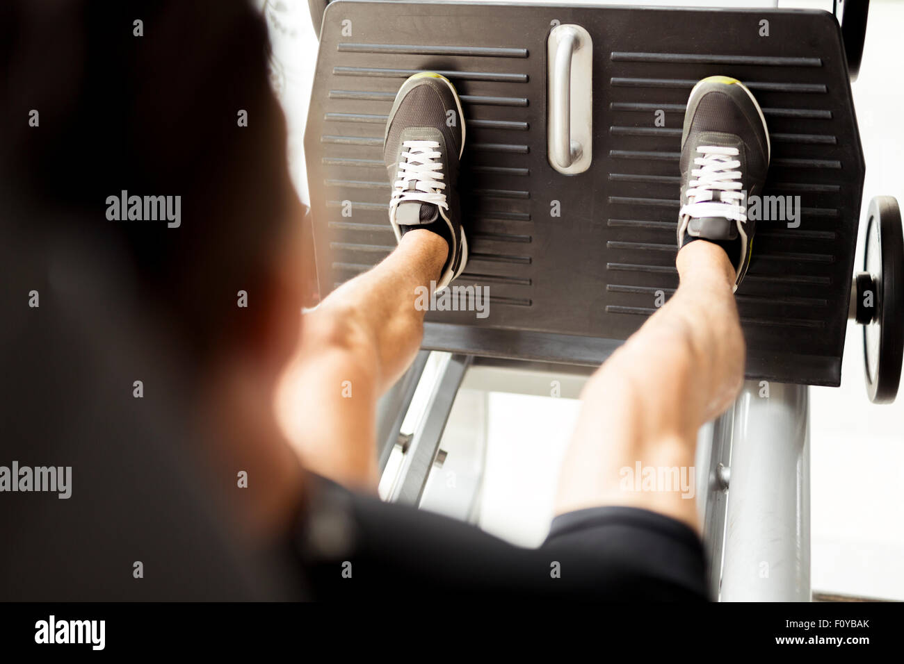 Young male working out in a gym and doing leg exercises - Stock Image