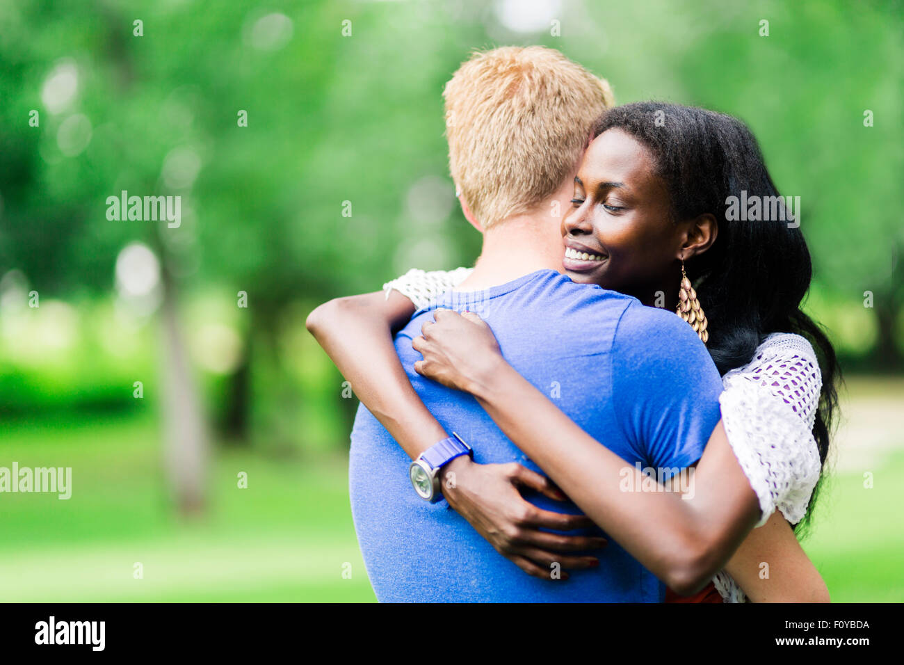 Couple in love hugging peacefully outdoors and being truly happy. Feeling of security and serenity - Stock Image