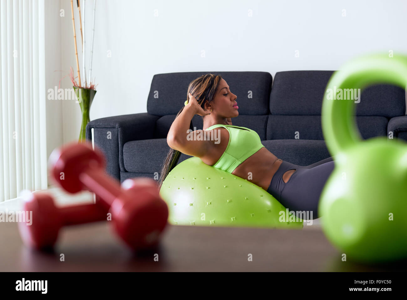Young adult african american woman in sports clothing at home, doing domestic fitness and training abdominals on swiss ball in l Stock Photo