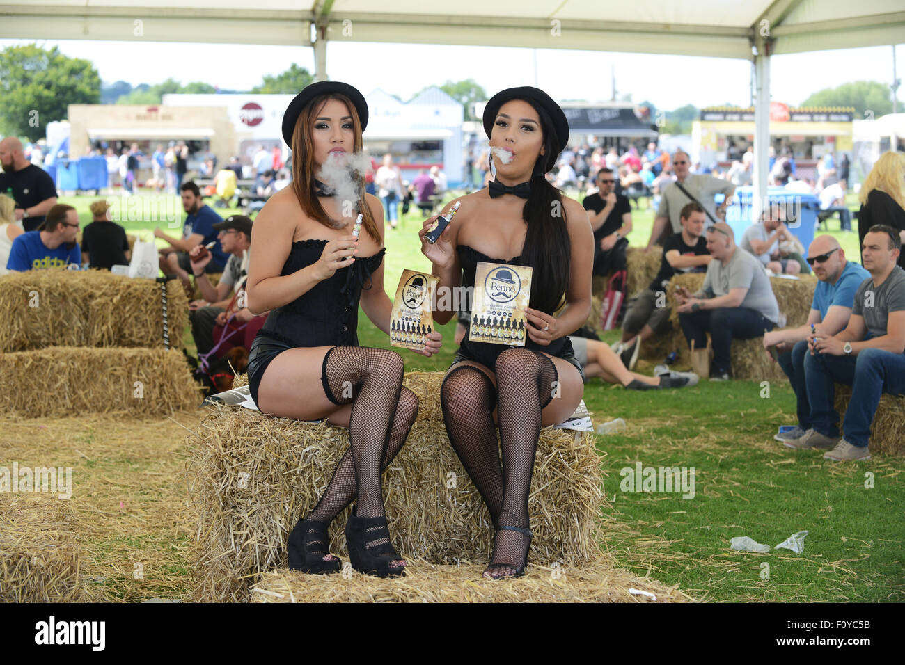 Models vaping electronic cigarette e-cigarette at Uk Vapefest 2015 while marketing Perino hand crafted e-liquid - Stock Image