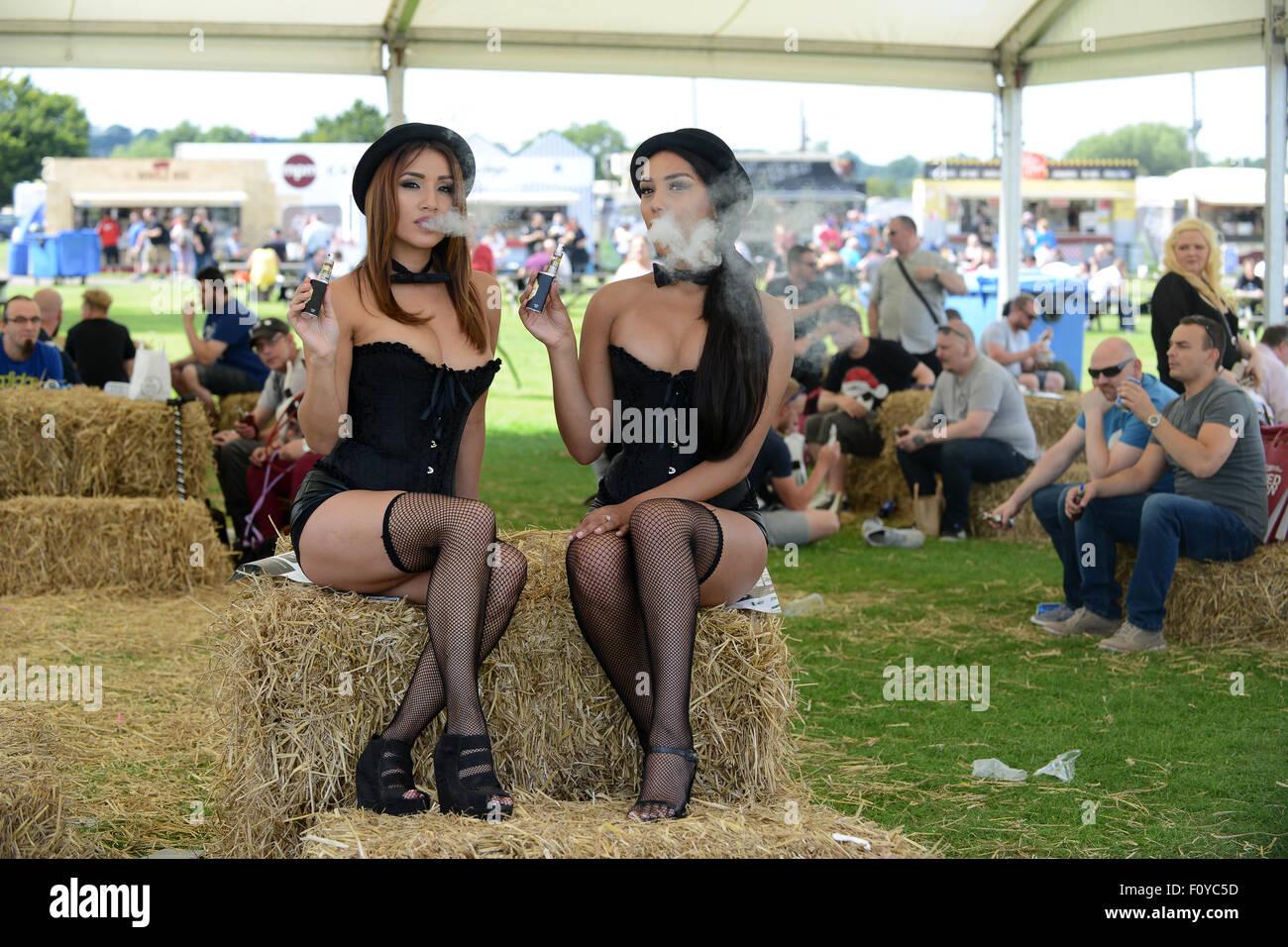 Models vaping electronic cigarette e-cigarette at Uk Vapefest 2015 while marketing Perino hand crafted e-liquid - Stock Image