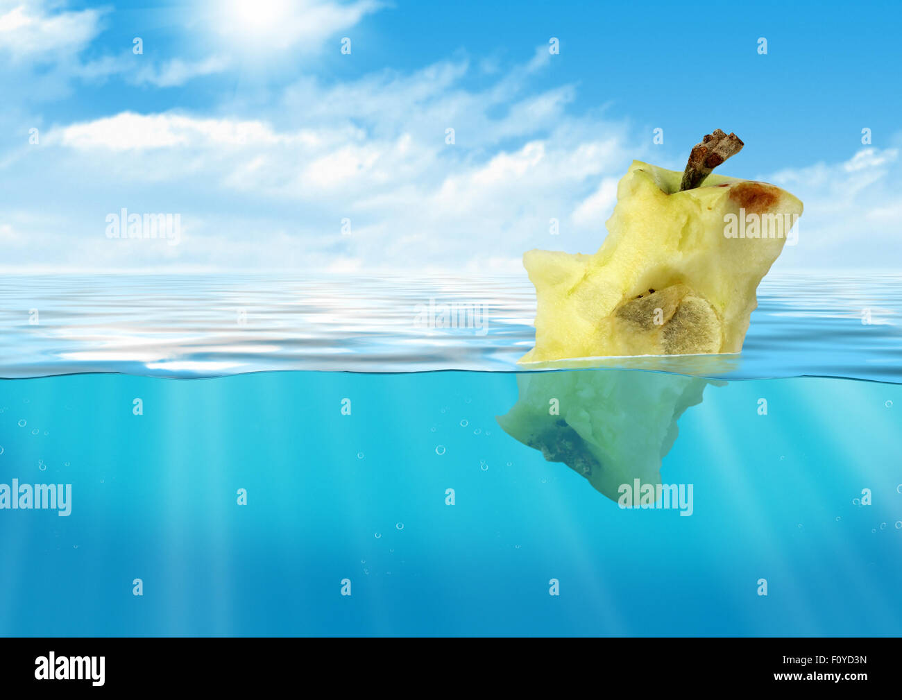 Bitten apple floating at sea, reservoir pollution concept - Stock Image