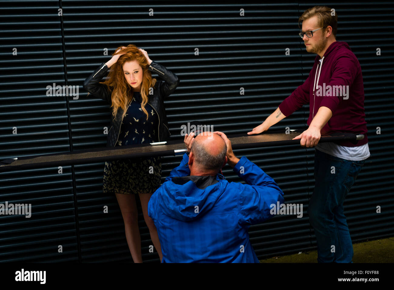 A young attractive red haired redhead ginger haired woman girl being  photographed by an amatuet photographer