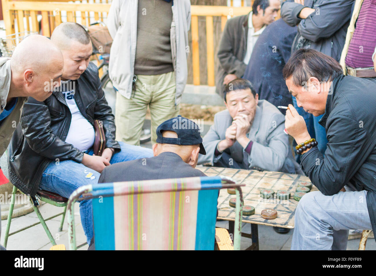 Chinese men spending time outdoors playing xiangqi (Chinese chess). - Stock Image