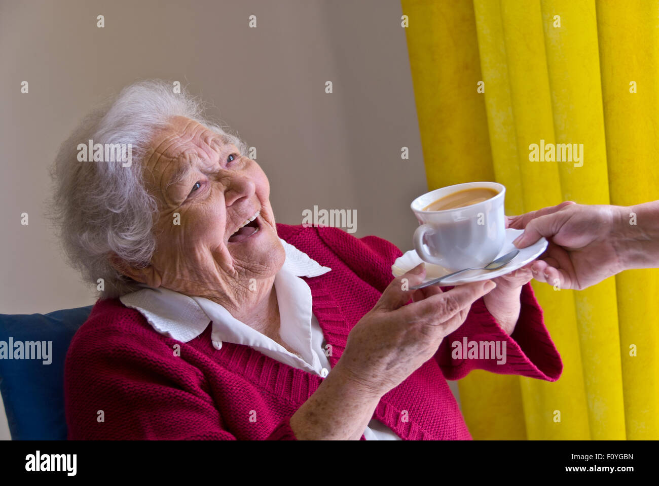 ELDERLY HAPPY TEA CARE CARER HOME VISIT Happy laughing elderly lady receiving a cup of tea from carer nurse companion - Stock Image