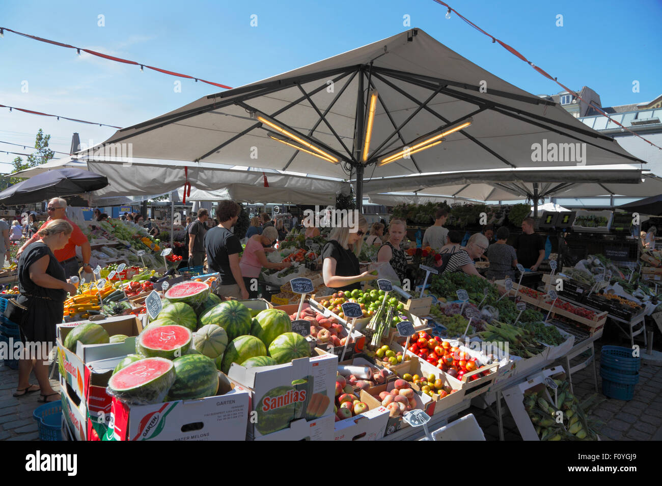 Fruit and vegetable stalls at Torvehallerne, the covered food market,  at Israels Plads in Copenhagen on a sunny - Stock Image