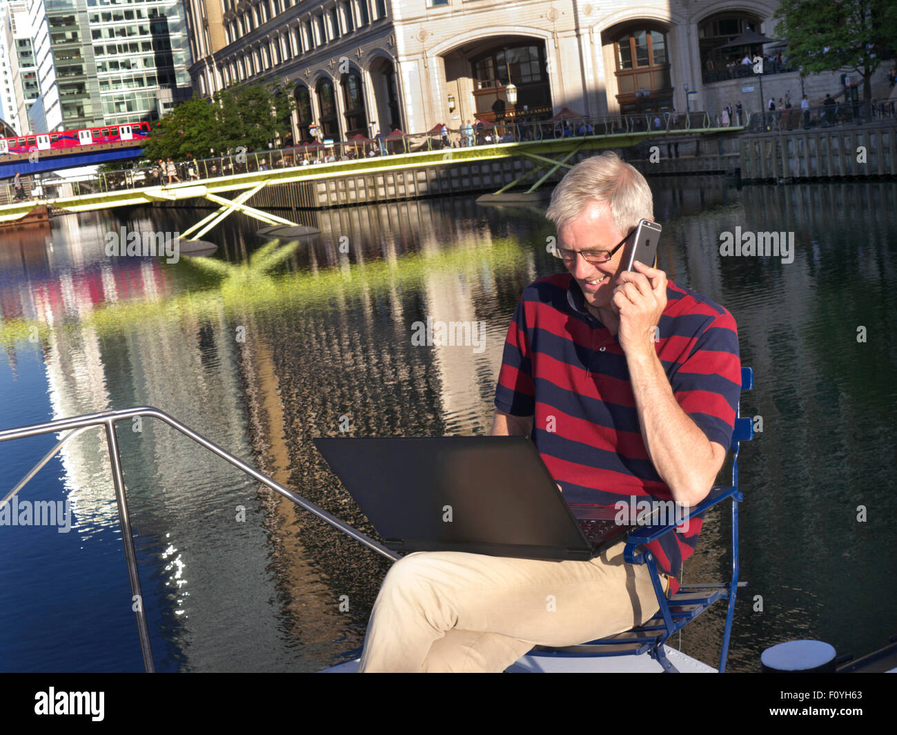 Mature man outside on his boat talking on iPhone 6 smartphone looking at his laptop computer Canary Wharf behind - Stock Image