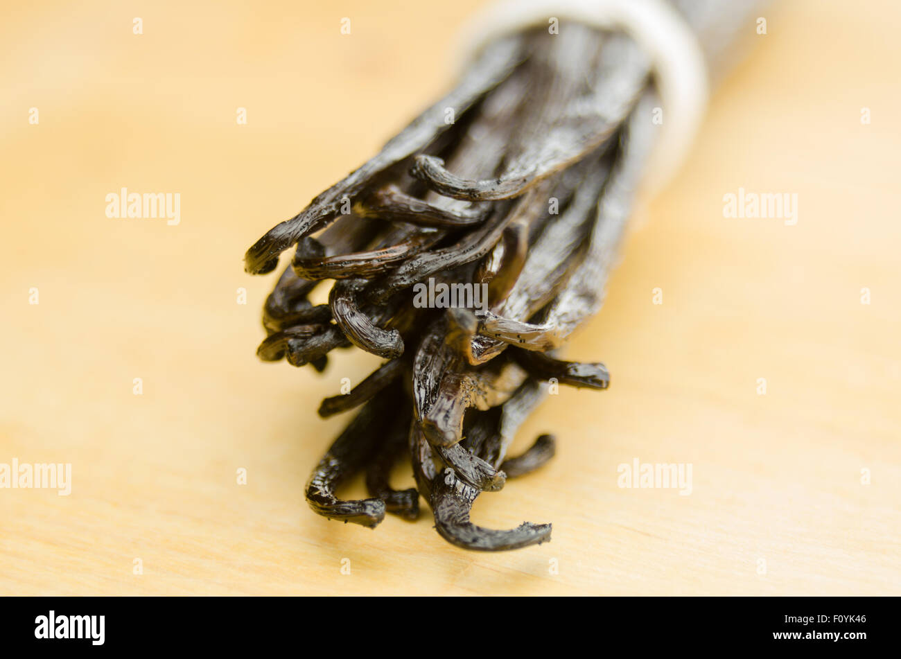 A bound group of vanilla beans against a bamboo butcher block - Stock Image