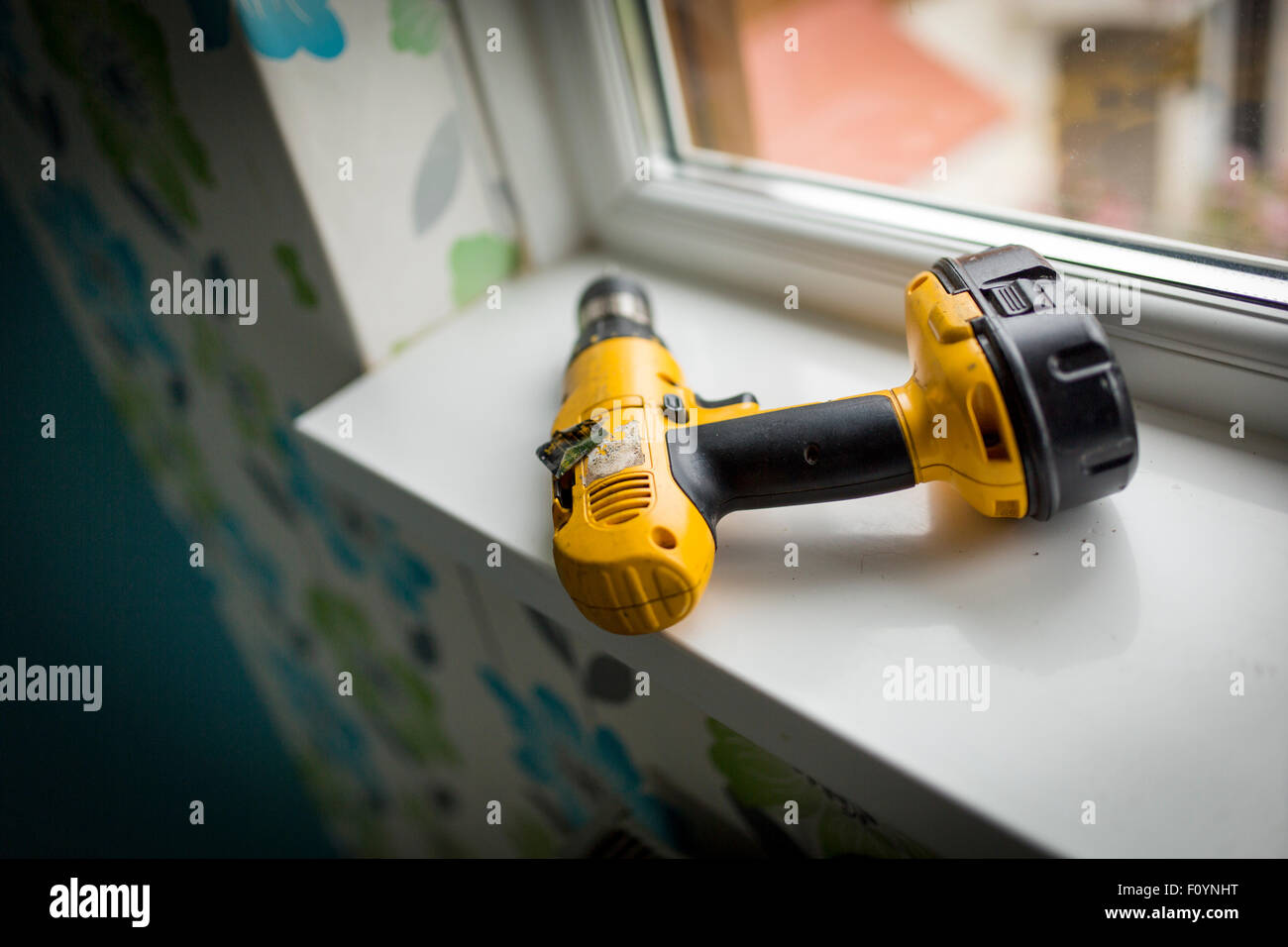 a power drill on a windowsill - Stock Image