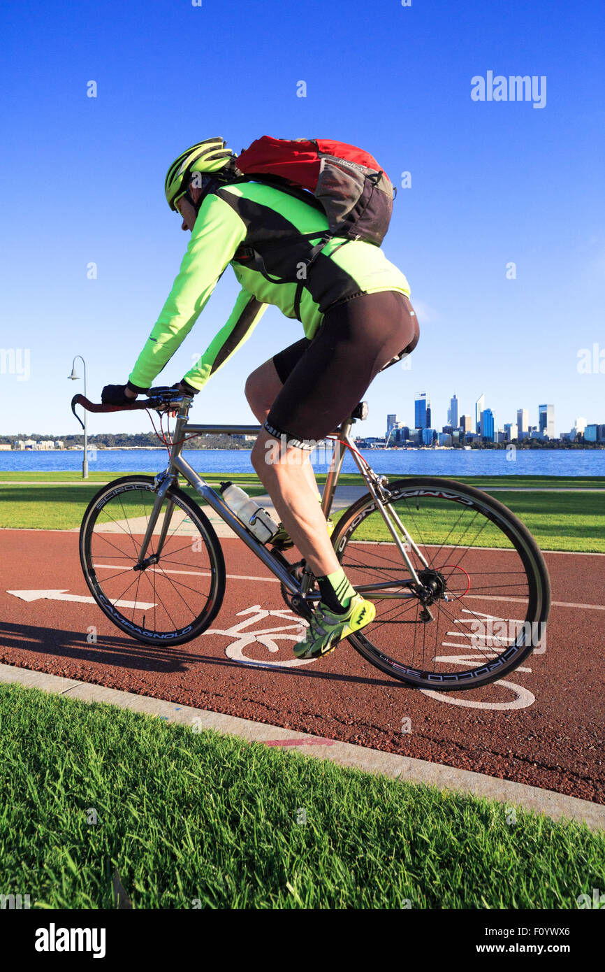 A male cyclist with a backpack riding down a bike path with a city skyline in the distance - Stock Image