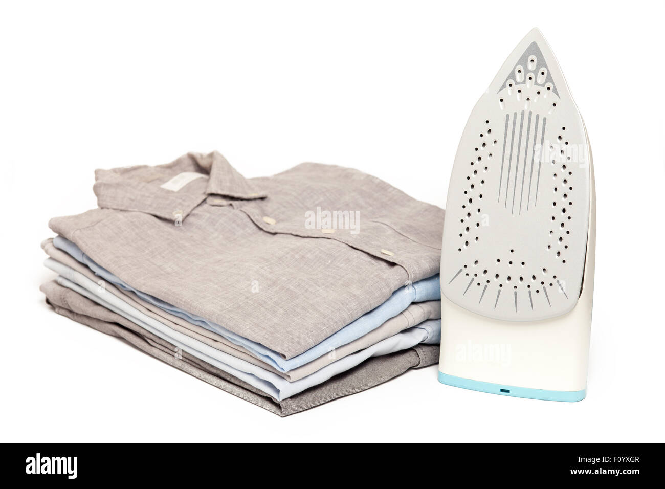 ironing housework ironed folded shirts clean concept still life garment apparel cloth indoors white background - Stock Image