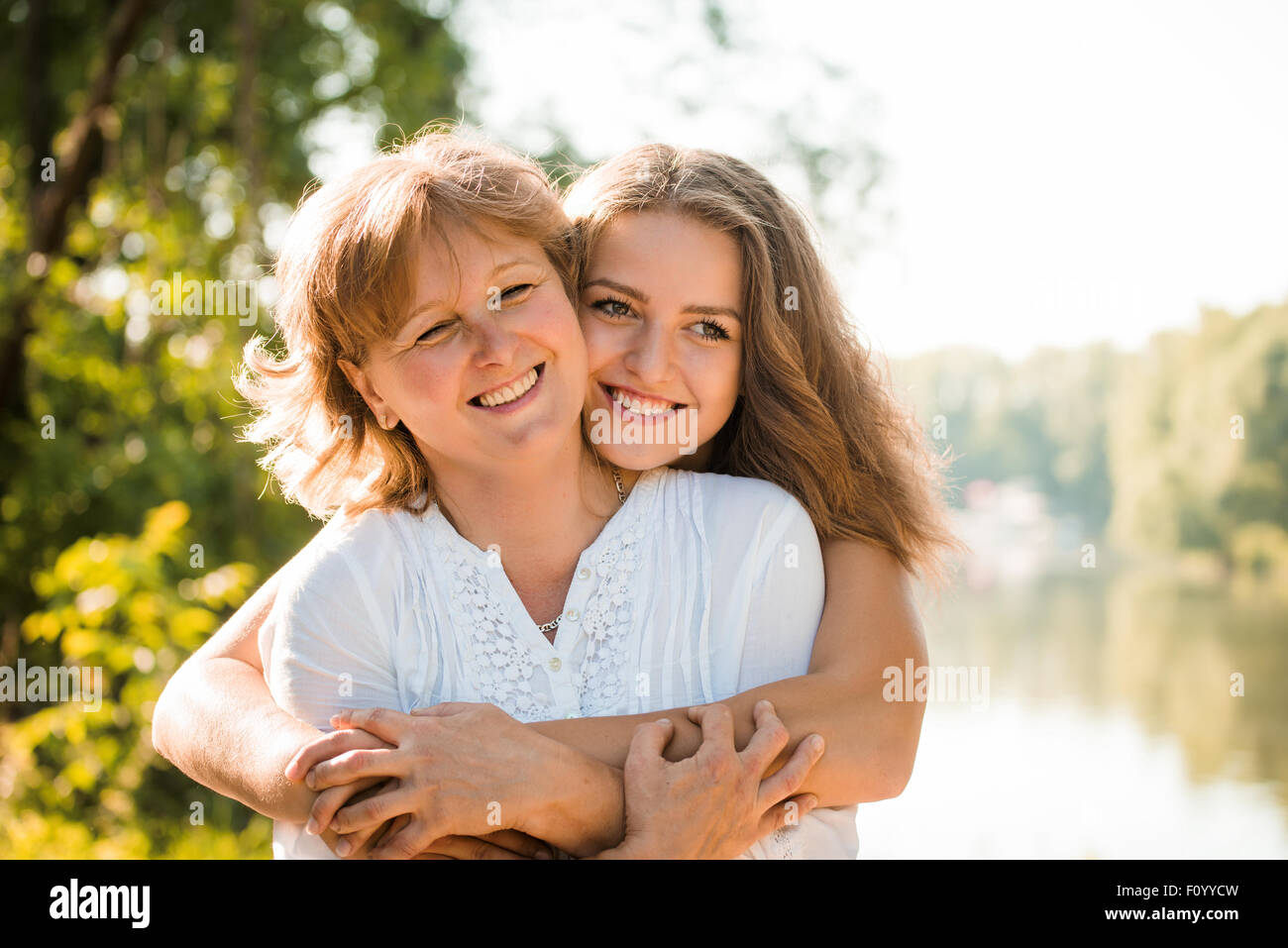 Mature mother hugging with her teen daughter outdoor in nature on sunny day - Stock Image