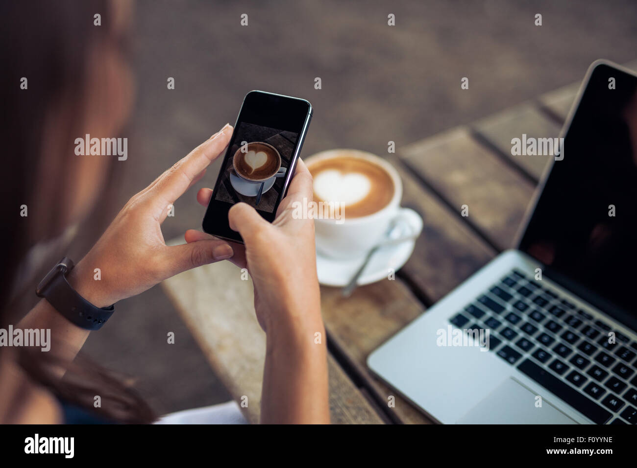 Woman taking a picture of a coffee cup with her smart phone while sitting at a coffee shop. - Stock Image
