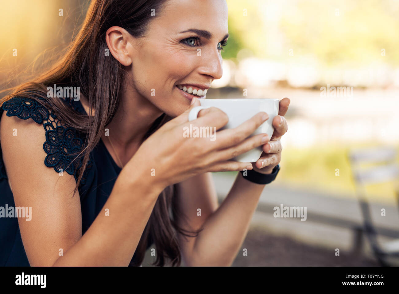 Young woman holding a cup of coffee and looking away smiling. Caucasian female drinking coffee at cafe. - Stock Image