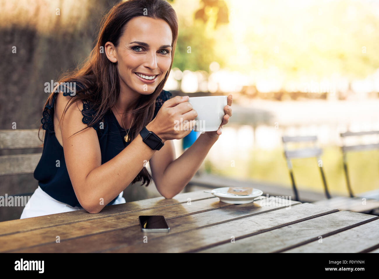 Portrait of beautiful young woman sitting at a table with a cup of coffee in hand looking at camera smiling while Stock Photo