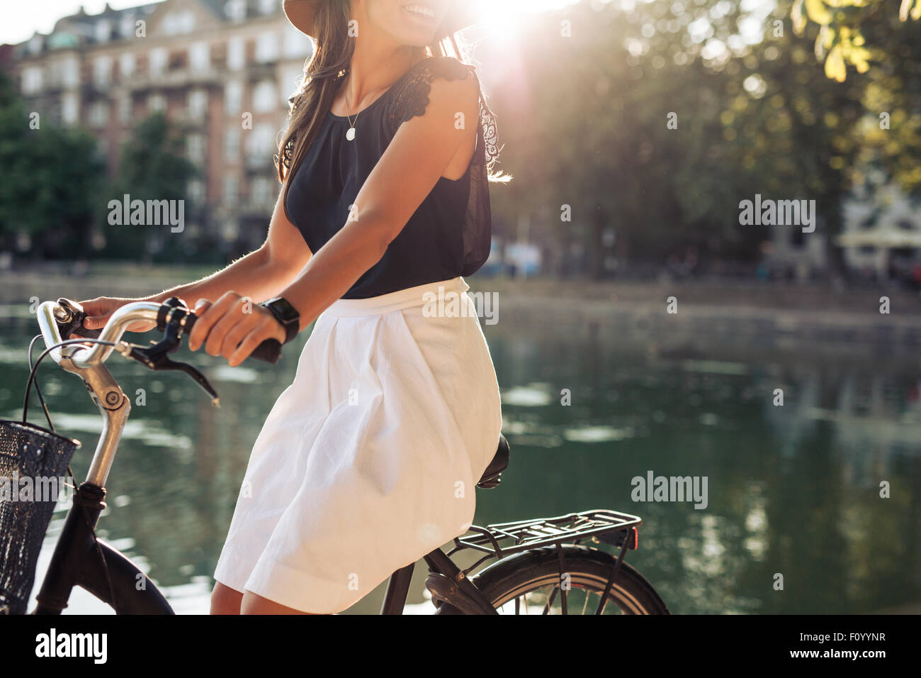 Cropped shot of young woman cycling by a pond. Woman on a summer day riding her bicycle. - Stock Image