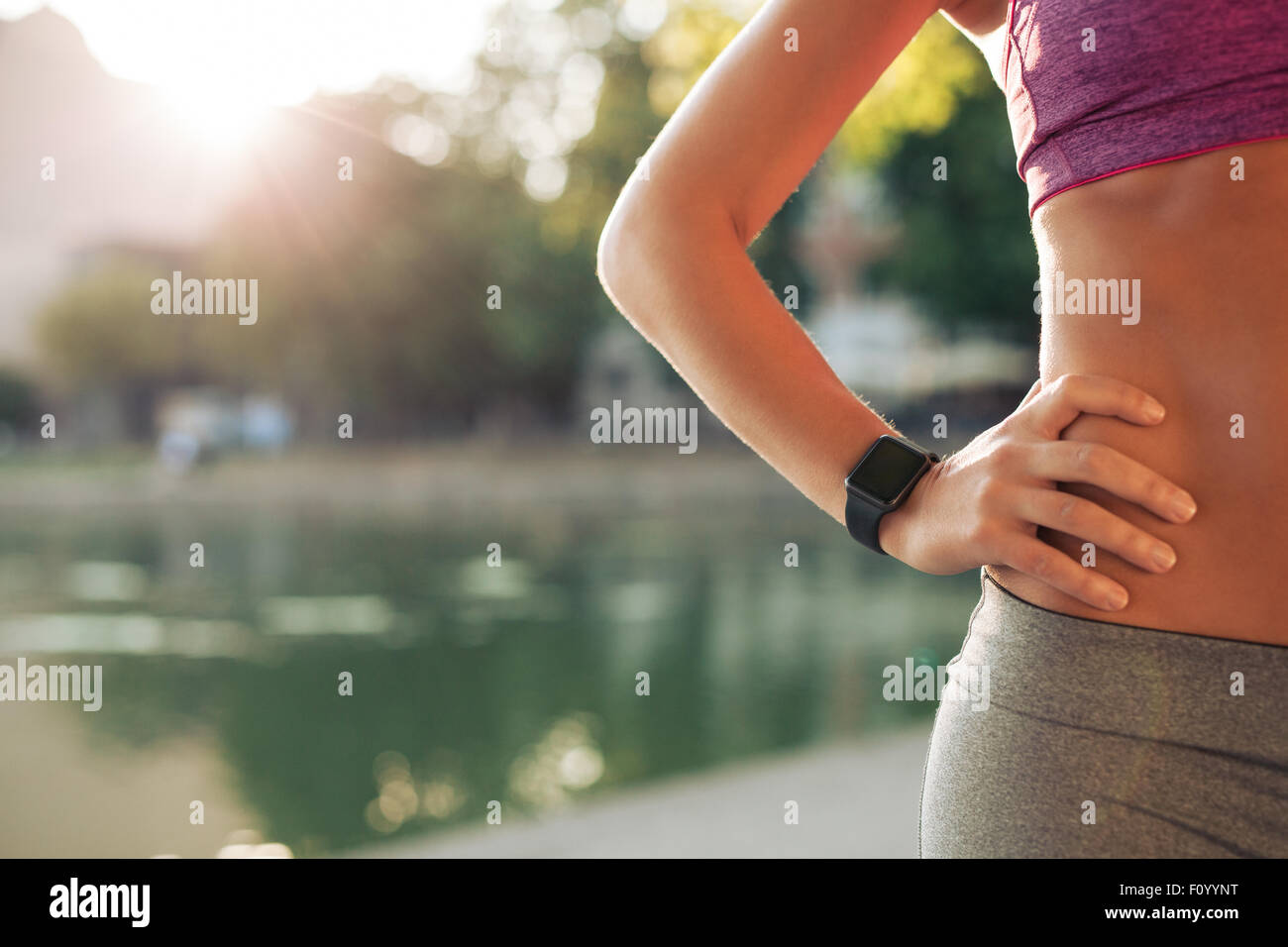 Sportswoman wearing smartwatch device. Cropped shot of fit woman in sports wear standing with her hand on hip outdoors, - Stock Image