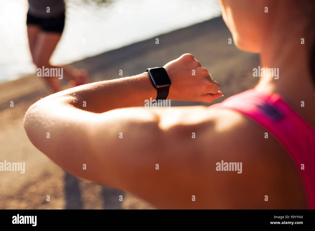 Close up shpt of sportswoman looking at her stopwatch. Jogger checking time on her smartwatch. - Stock Image