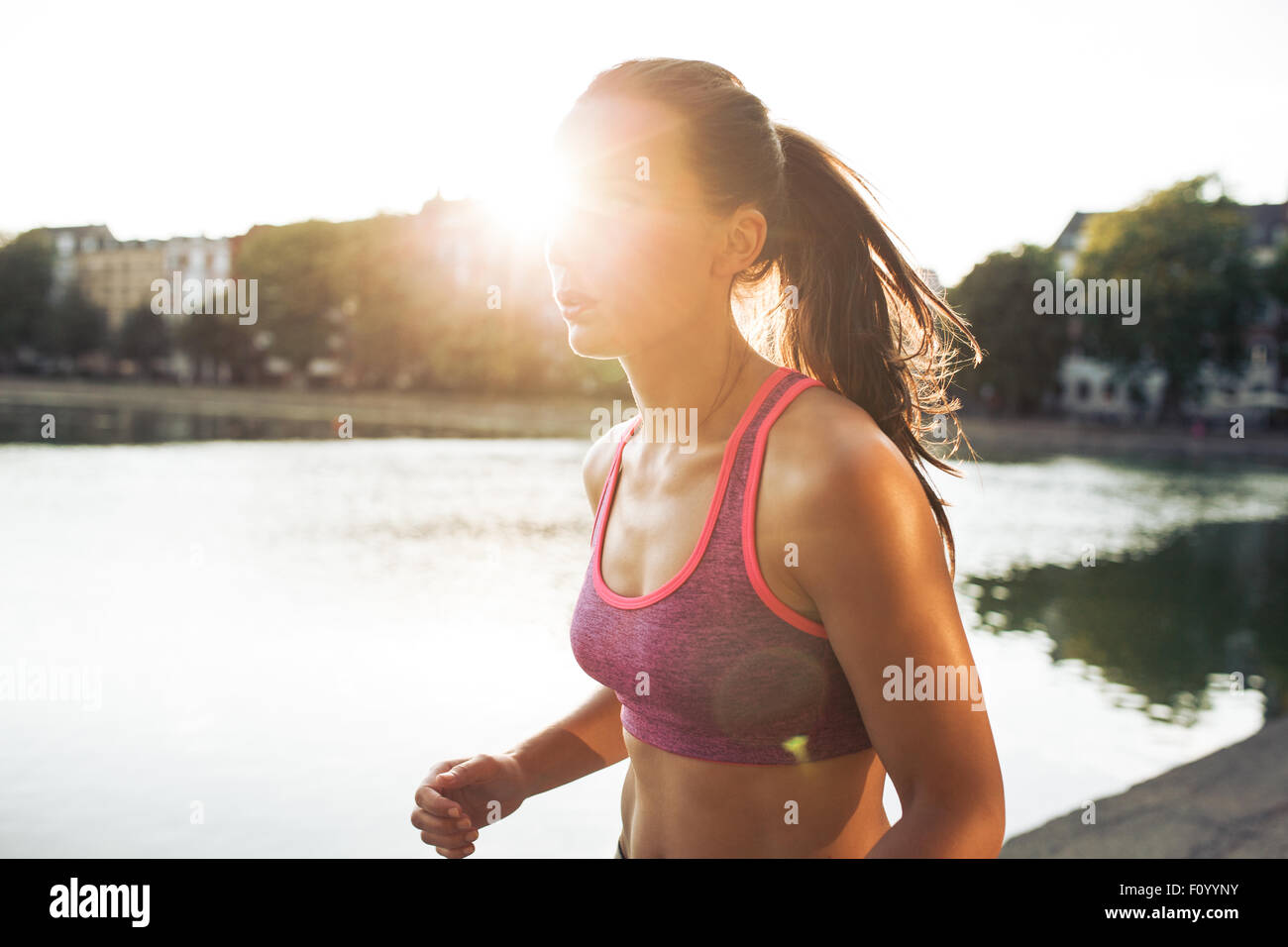 Outdoor shot of determined young woman out for a run in city park. Sportswoman jogging on a summer day with sun - Stock Image