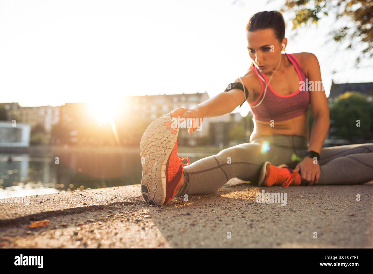 Fitness woman stretching before a run. Young female runner stretching her muscles before a training session. She - Stock Image