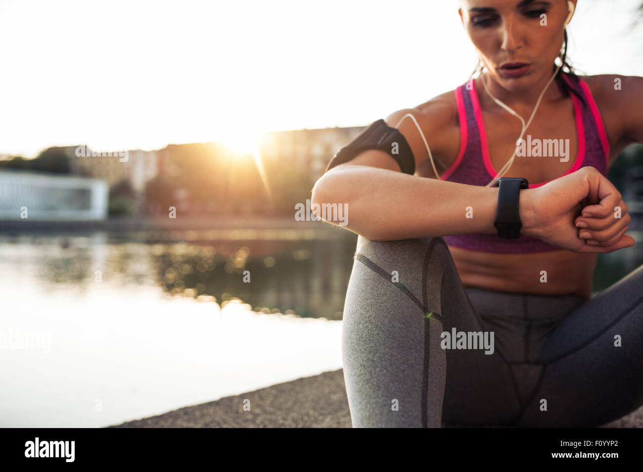 Beautiful young woman sitting outdoors using a smartwatch to monitor her progress. Caucasian female runner resting - Stock Image