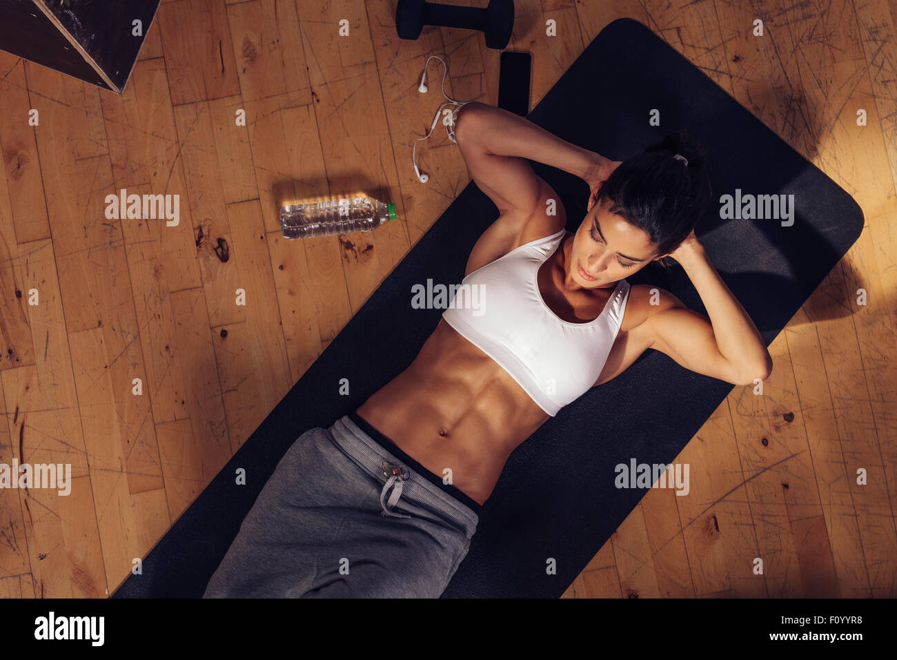 Sporty young woman lying on yoga mat doing sit-ups in gym. Top view of muscular woman doing abs crunches. - Stock Image