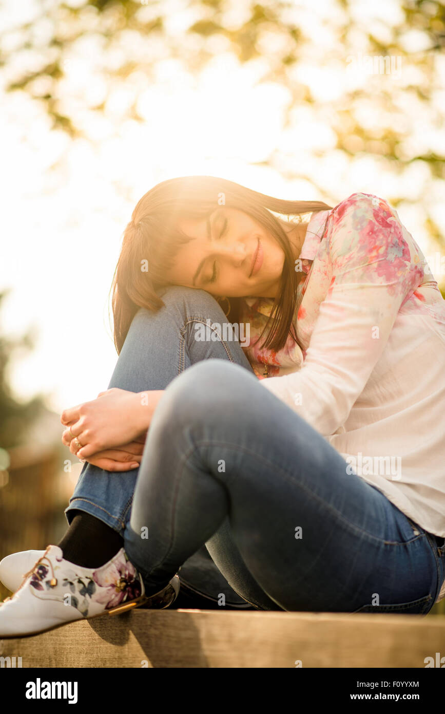 Portrait of woman leaning on her knee with closed eyes sitting on bench at sunset - Stock Image