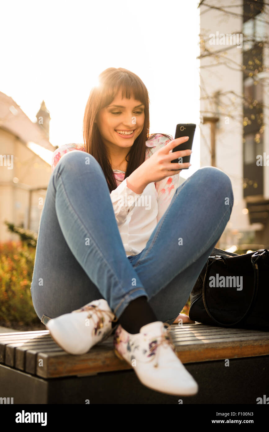 Young smiling woman looking to her phone in street with sun in background - Stock Image