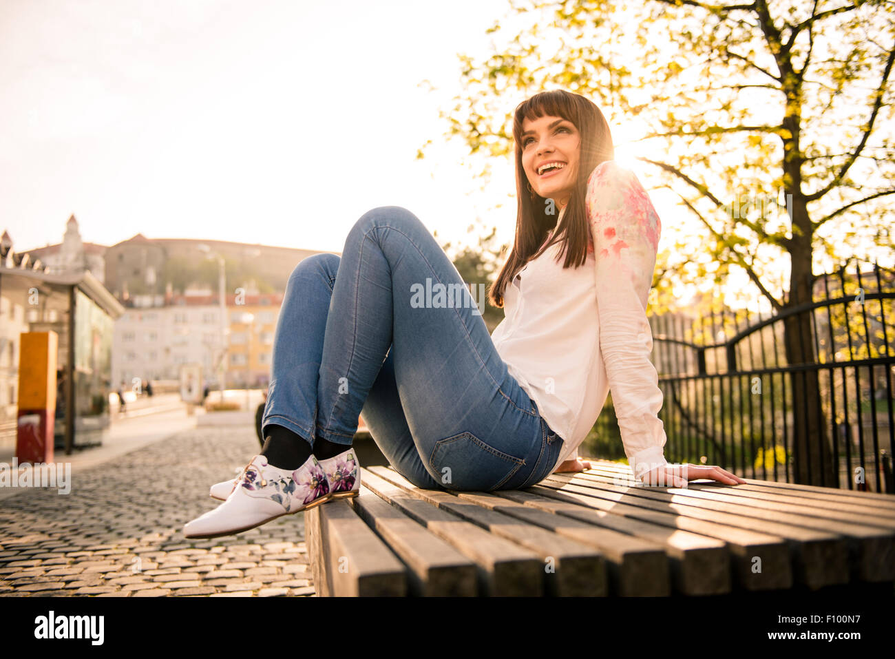 Young woman sitting on bench in street and enjoying life with sun in background - Stock Image