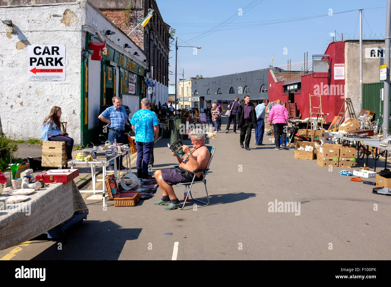 Antique dealer sunbathing on the street at his stall in The Barras, Glasgow's famous secondhand market, Glasgow, - Stock Image