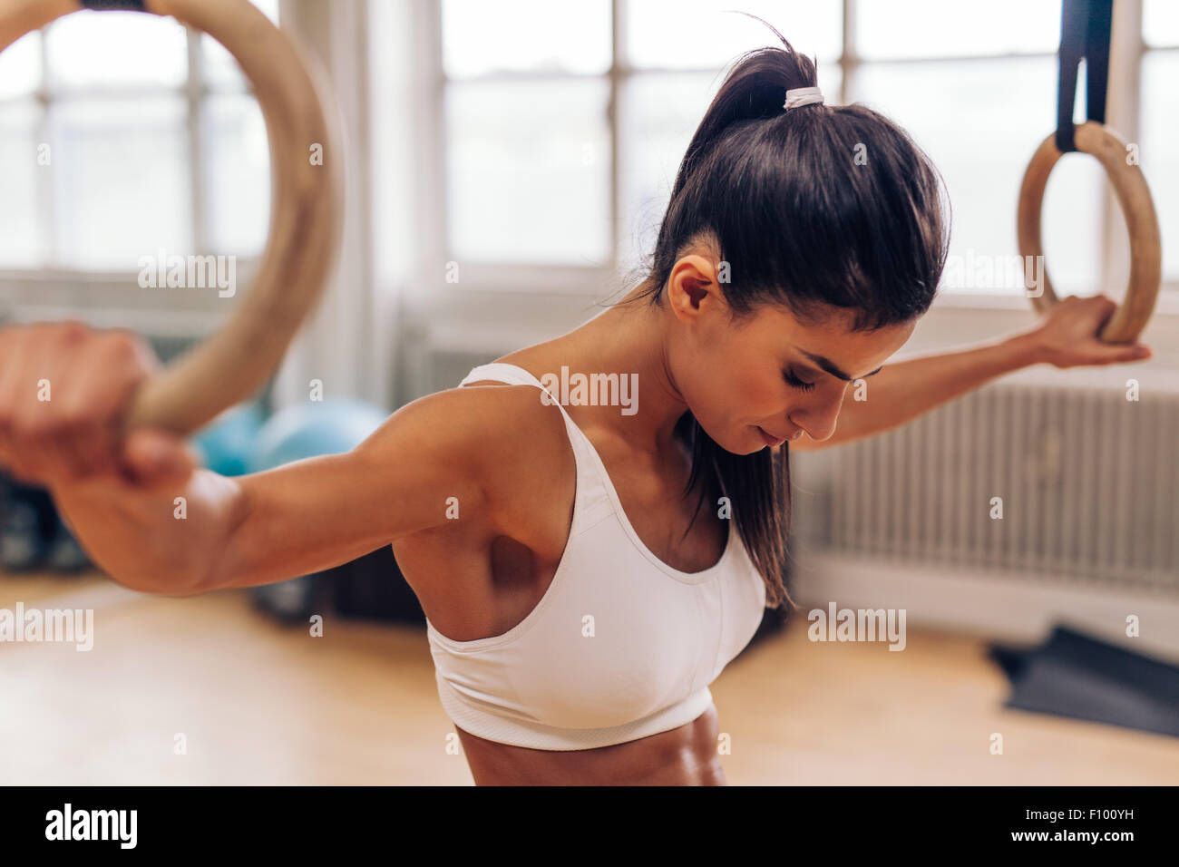 Fit young woman holding gymnast rings at the gym. Strong young woman exercising at gym. - Stock Image