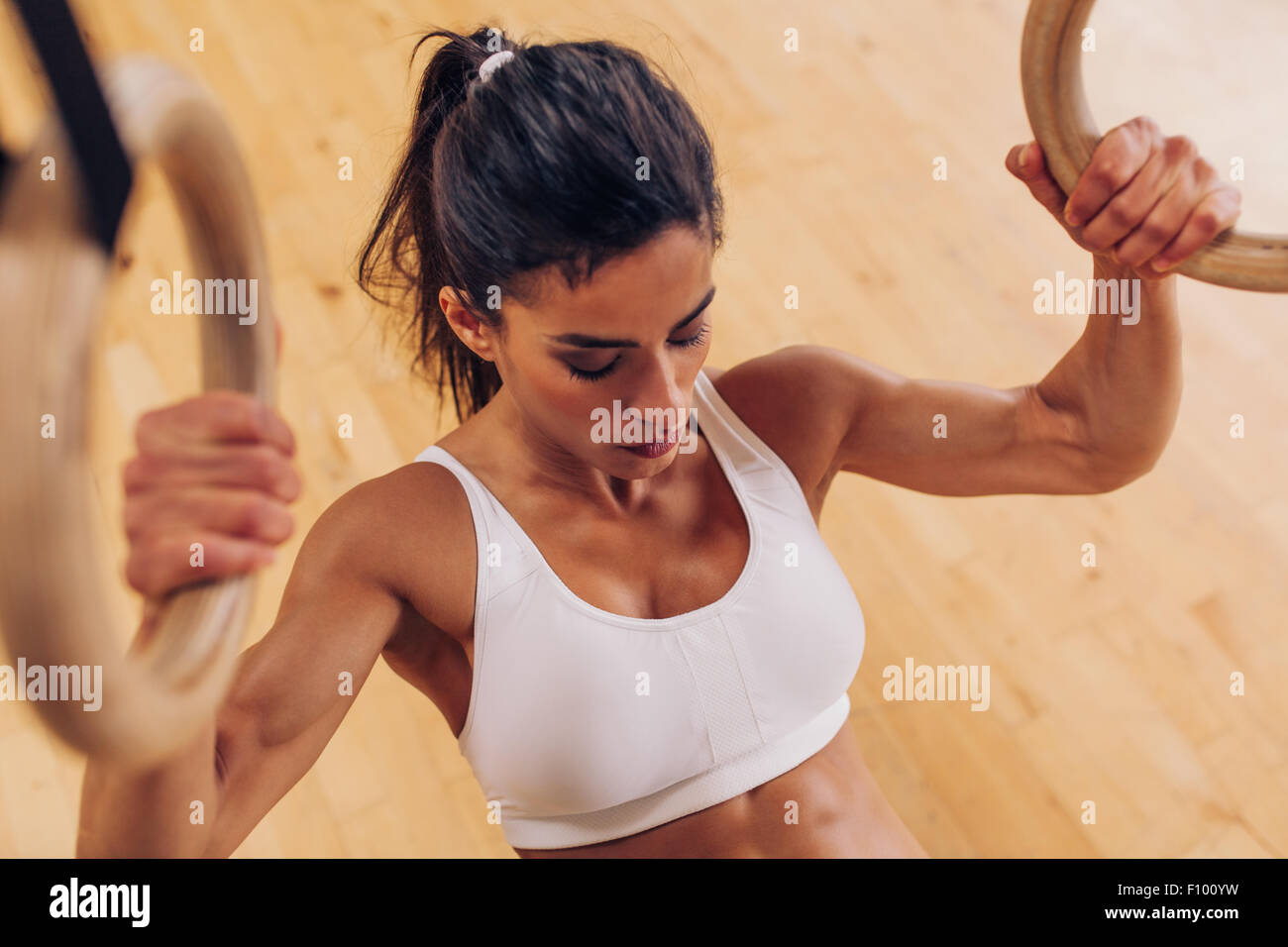 Image of strong young woman doing pull-ups exercise using gymnastic rings at gym. - Stock Image