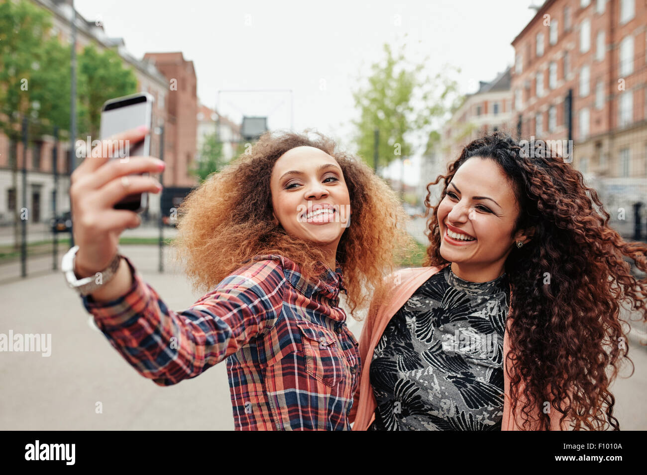 Two beautiful young women taking a picture together on city street. Young female friends taking a selfie using mobile Stock Photo