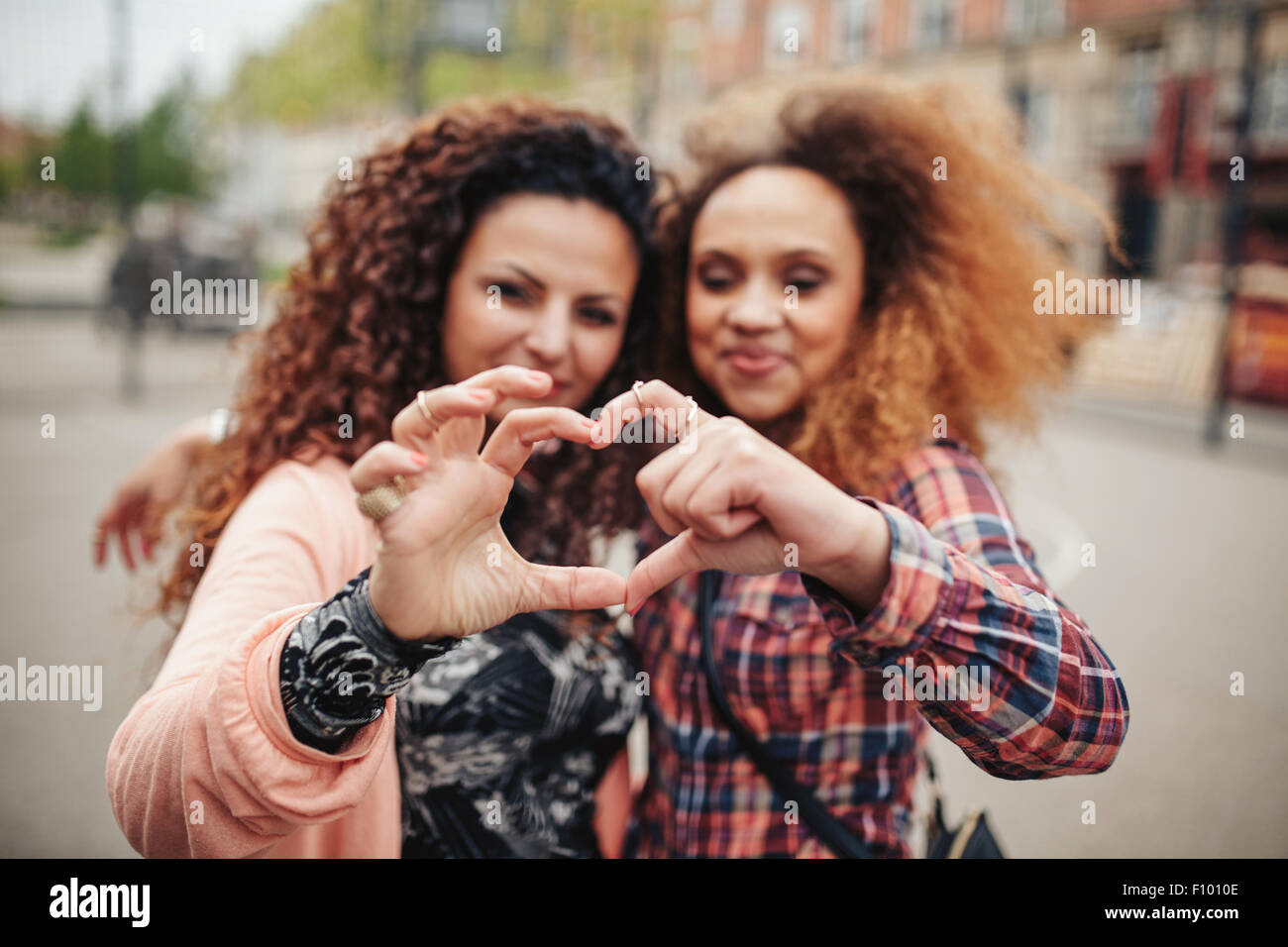 Happy young female friends making heart shape with hands and fingers. Two women standing together outdoors on city - Stock Image