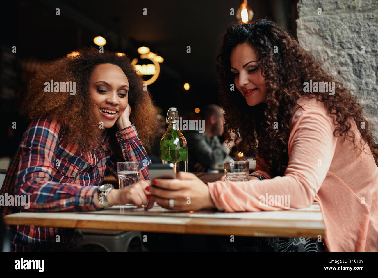 Portrait of  young women sitting at a cafe using mobile phone. Two young girls reading a text message on mobile - Stock Image