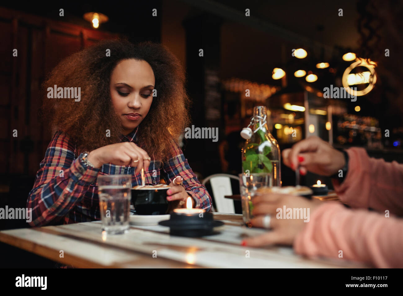 Shot of young african woman sitting at a restaurant stirring her coffee. Girl having coffee in a cafe - Stock Image