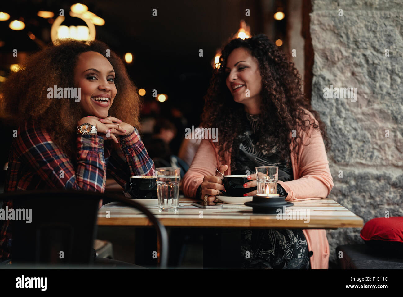 Two women sitting at a restaurant smiling. Young friends in a cafe, with one looking at camera smiling. - Stock Image