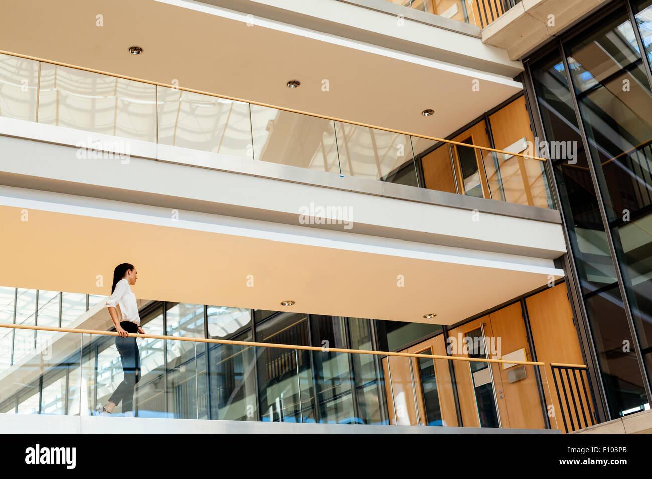 Elegant businesswoman walking  from one door to another - Stock Image