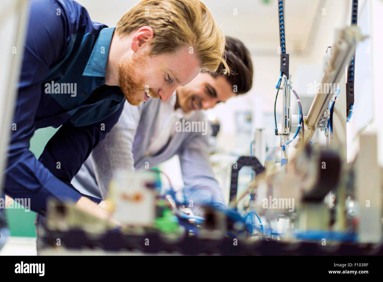 Two young handsome engineers working on electronics components and fixing broken chips - Stock Image