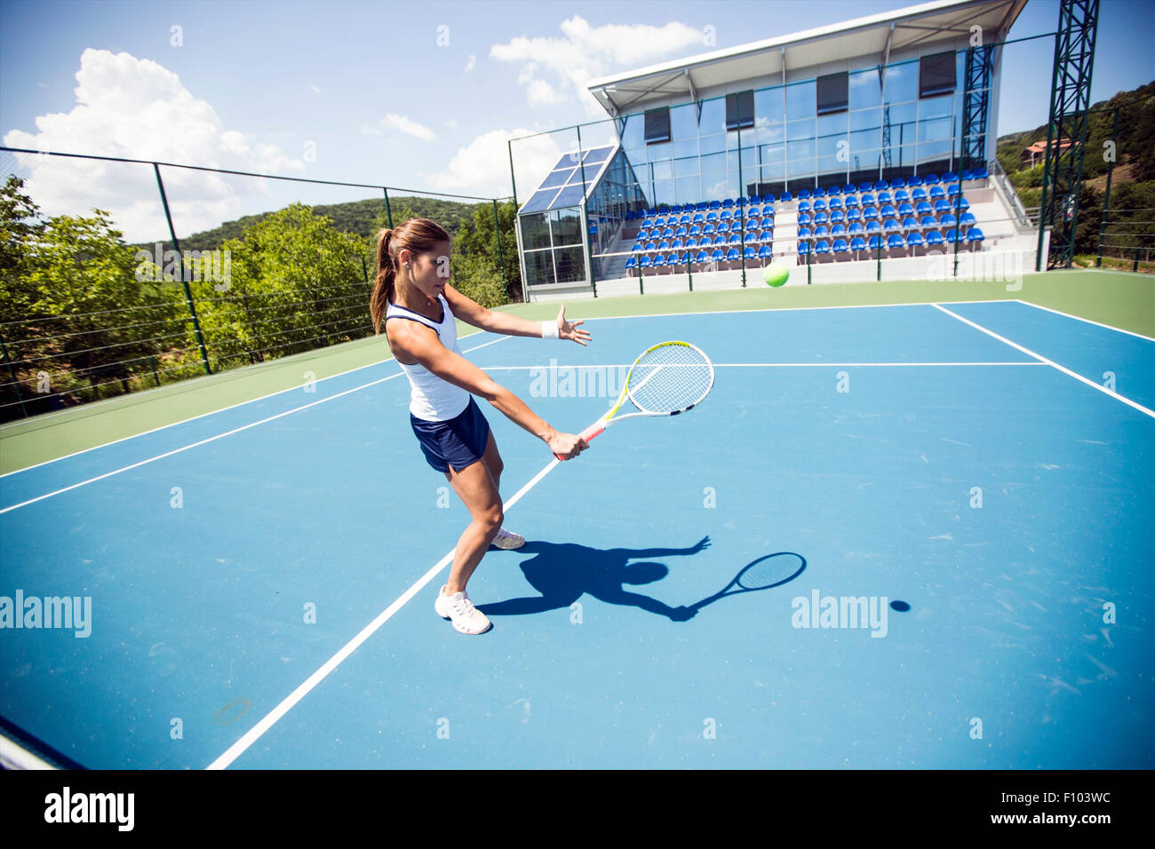 Female tennis player performing a drop shot on a nice blue court Stock Photo