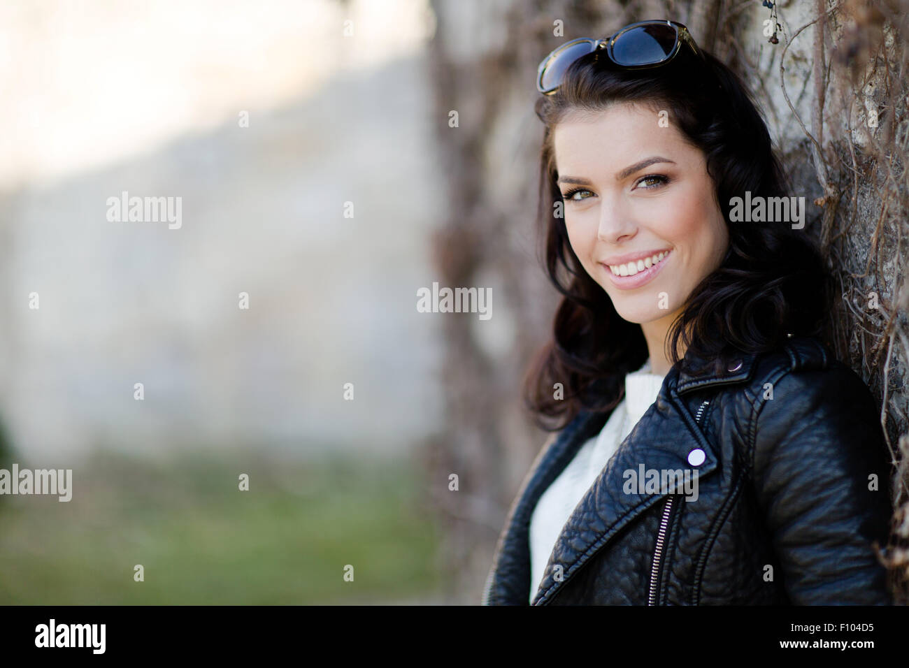 Portrait of a smiling, beautiful young woman leaning against a wall - Stock Image