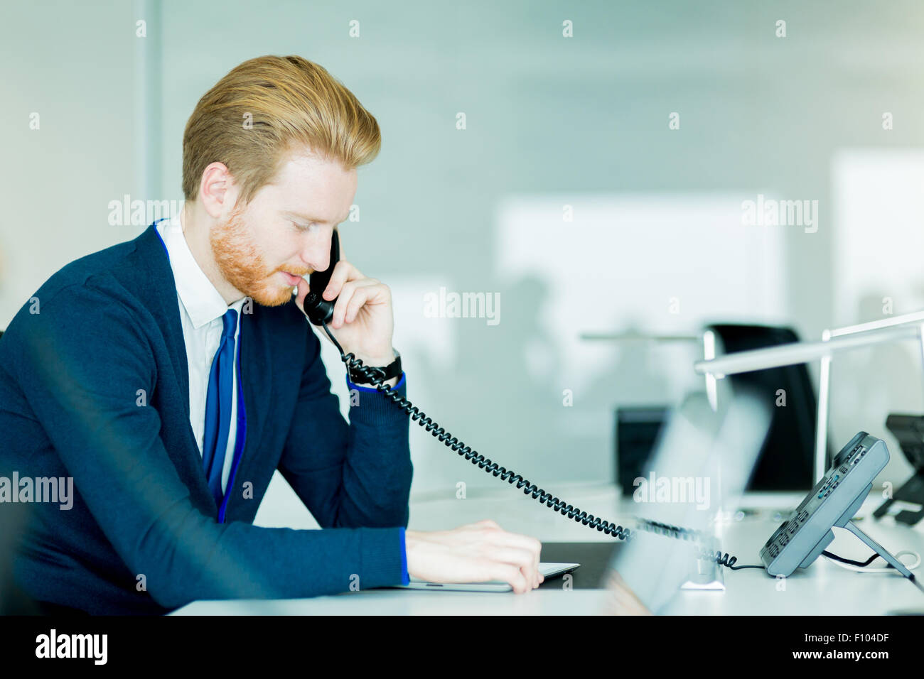 A handsome male, red haired worker in a call center office talking on a phone - Stock Image
